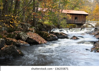 Stream flows under old wooden covered bridge, during autumn in New Hampshire. It is a popular attraction in New England.
