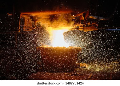 A stream of hot metal pours into the ladle. Electric arc furnace shop EAF. Metallurgy.