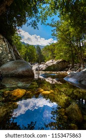 Stream with reflections in natural scenic landscape. Surrounded by nature with rocks, trees and river with water mirror. Some clouds in the blue sky.