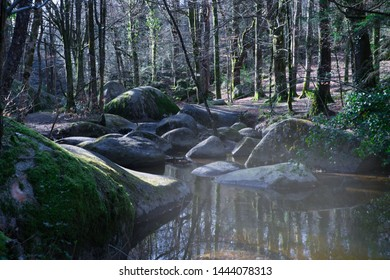 Stream running between granite boulders with an early morning mist over the water. Sinister mood.