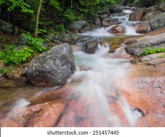 A stream rushes through the forest, splashing over boulders, down New Hampshire's scenic Franconia Notch.