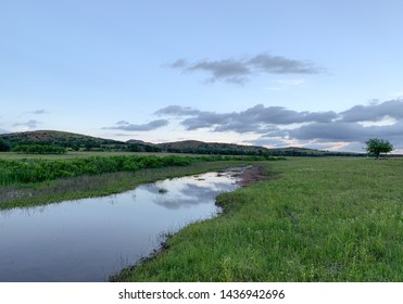 Stream through field with mountains and clouds n background in the Wichita Mountains Wildlife Refuge. Indiahoma, OK