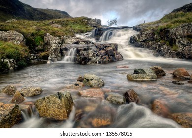 A stream tumbles down the mountainous hillside across rustic rock in Glen Coe.  Glen Coe is a glen in the Highlands of Scotland.