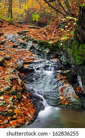 A stream tumbles down a rocky ravine surrounded by vibrantly colorful autumn leaves. Shot near Indiana's Cagle's Mill Lake.