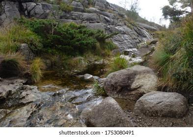 Ein Wasserstrom zwischen Felsen in den Bergen