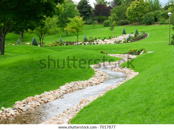 stream of water flowing through grassy hills with trees