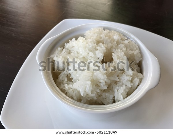 Streamed sticky rice in a bowl on wooden table.