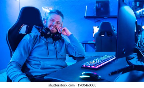 Streamer young man rejoices in victory professional gamer playing online games computer with headphones, neon color.