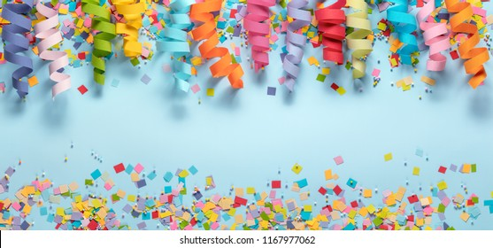 Streamers and confetti on blue background.Birthday decoration.