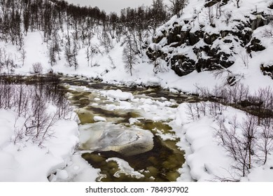 A streaming winter river in the mountains of Setesdal, Norway. River is surrounded by trees, snow and ice