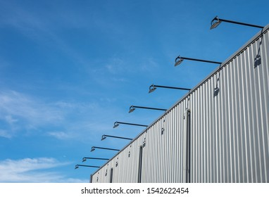 Street architecture outdoor lamp hanged and cantilevered from the wall of the building which is metal sheet with blue sky background.