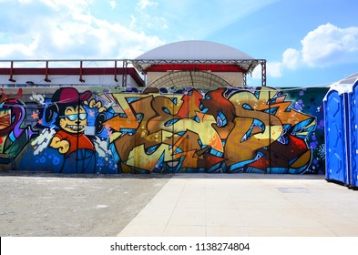 Street art. Abstract background image of a full completed graffiti painting in beige and orange tones with cartoon character.