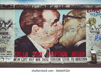 Street art graffiti painting 'The Kiss' by Dmitri Vrubel at famous East Side Gallery, the longest preserved section of Berlin wall, with retro vintage Instagram style filter effect, Berlin, Germany