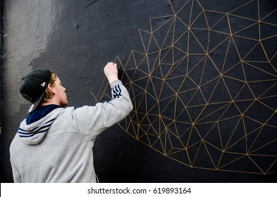 STREET ART, SHOREDITCH, LONDON, 28th JANUARY 2016. An artist creating an artwork on the wall with strings.