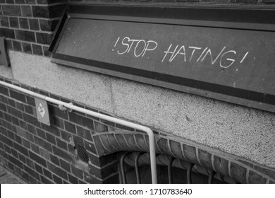 street art of as simple wording. Stop Hating drawn onto a building as meaningful graffiti.
