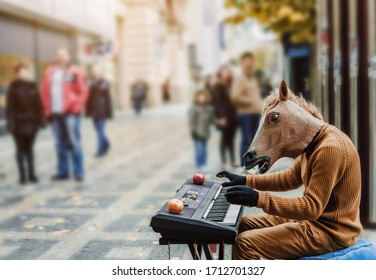 A street artist with a masked horse's head plays the piano. Backgrond contains blured people which are looking to the artist performance. Musical perfomer player with horse head.