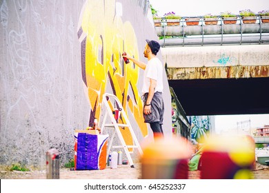 Street artist painting a colorful graffiti on a grey wall under bridge - Young graffiter writing and drawing murales with yellow spray - Urban, lifestyle and modern art concept