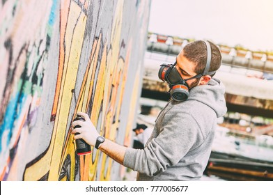 Street artist painting colorful graffiti on a wall under the bridge - Urban man performing with murales - Concept of modern art - Focus on his hand