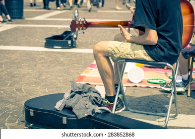 Street artist plays guitar - art, lifestyle and music concept