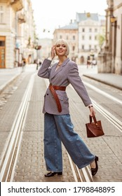 Street autumn fashion portrait of elegant happy smiling woman wearing trendy checkered blazer, wide belt, wide leg jeans, holding brown top handle bag, walking in street of European city