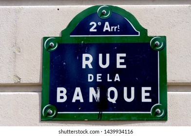 Street Bank. White and blue street name sign on a stone facade. Paris, France. French text: Rue de la Banque.