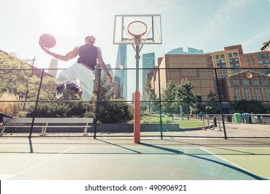 Street basketball athlete performing huge slam dunk on the court, New york buildings background