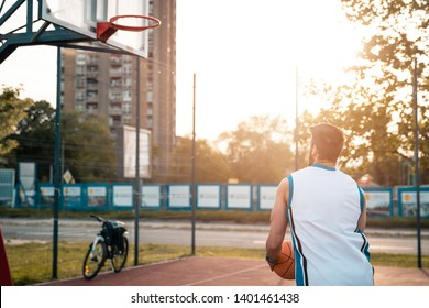 Street basketball player shooting on outdoor court. Urban background at sunset.