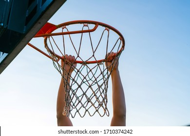 Street basketball slam dunk competition. Close up of player hanging on the hoop. Urban youth game. Concept of success, scoring points and winning