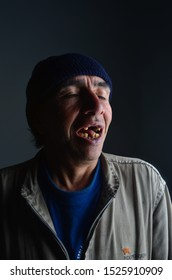 the street beggar man smiles openly with very few teeth. Photo taken at the Photography studios of Laboom in Bogota Colombia On September 2013