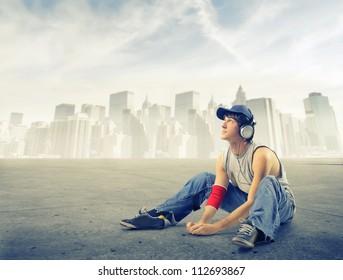 Street boy listening to the music on a ground near New York