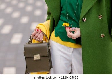 Street, bright style. A young girl in white trousers, warm greens polto. Yellow scarf. Green jacket. A brown handbag. Details. Flowers