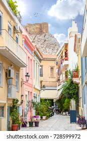 Street and buildings of the historic downtown of Athens, Greece with the Acropolis and greek flag on the background.