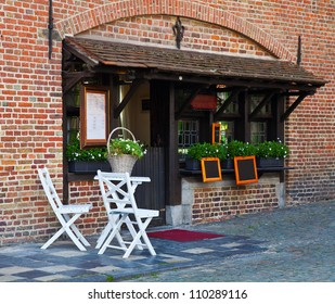 Street cafe in the ancient European city. Two white chairs and table stand near an entrance in cafe