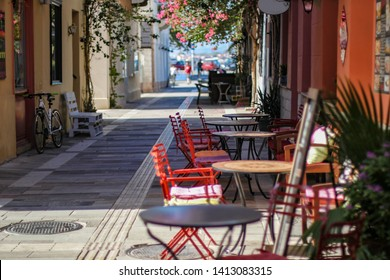 Street cafe with bright red chairs in Nafplio city, Peloponnese, Greece