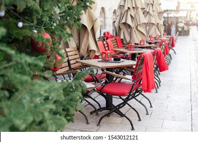 Street cafe near european Christmas tree with red ornaments outdoor. Cozy wooden tables and chairs with warm plaid at winter market in old town. Festive and New Year atmosphere in Europe