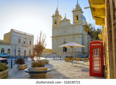 Street cafe and red telephone box in front of San Lawrenz parish church on Gozo island, Malta