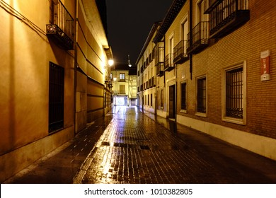 "Street called ""De la Imagen"" in Alcala de Henares, Madrid, Spain, on a very rainy and cold December night with the street very bright and with reflections of water and no people on the street"