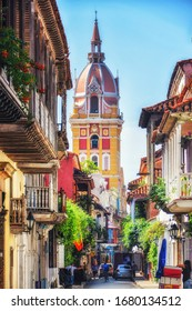 A street in Cartagena, Colombia with a lovely church tower overlooking a street with balconies shrouded in bougainvillia