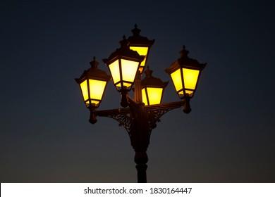 Street city cast-iron lantern lit at night, yellow lantern light on dark blue background.
