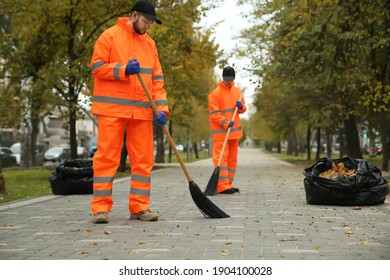 Street cleaners sweeping fallen leaves outdoors on autumn day