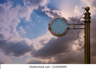 Street clock on sky background. Classic style streeet clock. 4 o'clock.