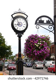 A street clock and an street sign with a big flowerpot hanging from it on a busy street in an small town.