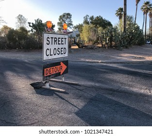 Street closed and detour signs on a sunny morning on a street with palm trees