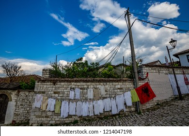 Street clothes sale in the old town of Berat, Albania along with the Albanian national flag, spring day with scenery cloudy sky