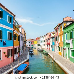 Street with colored houses on the island of Burano and with a canal in the middle, near Venice, Italy