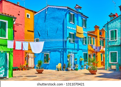 Street with colorful houses and airing clothes in Burano, Venice, Italy