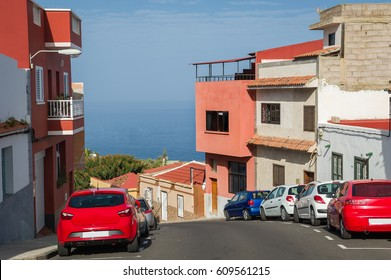 Street with colorful houses is going down the hill to the Atlantic ocean shore. Icod de los Vinos, Tenerife, Spain.