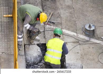street construction workers repairing sidewalks and pipelines