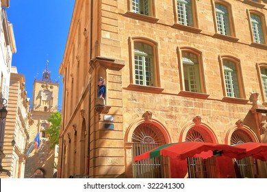 Street corner with traditional buildings and distant belfry in Aix-en-Provence, France