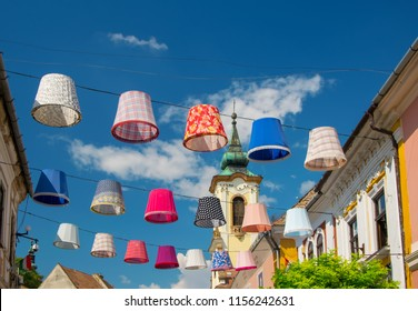 Street decoration of plenty colorful lampshades in old town of Szentendre, Hungary at sunny summer day. Szentendre is a town of arts and popular destination for tourists staying in Budapest